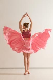 Young girl dancing in beautiful pink dress, back view. Professional dancer exercising in dance studio