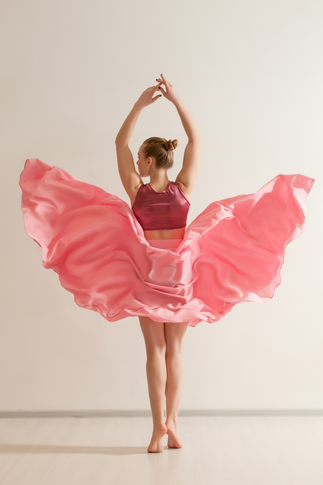 Young girl dancing in beautiful pink dress, back view. Professional dancer exercising in dance studio